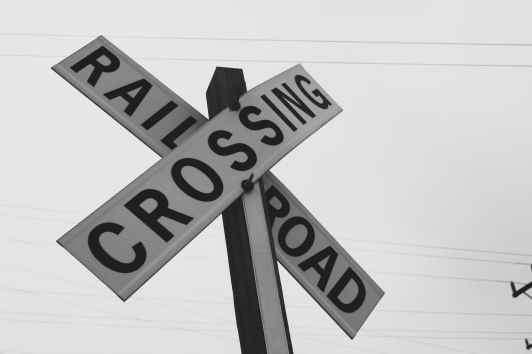 grayscale photography of railroad crossing signage